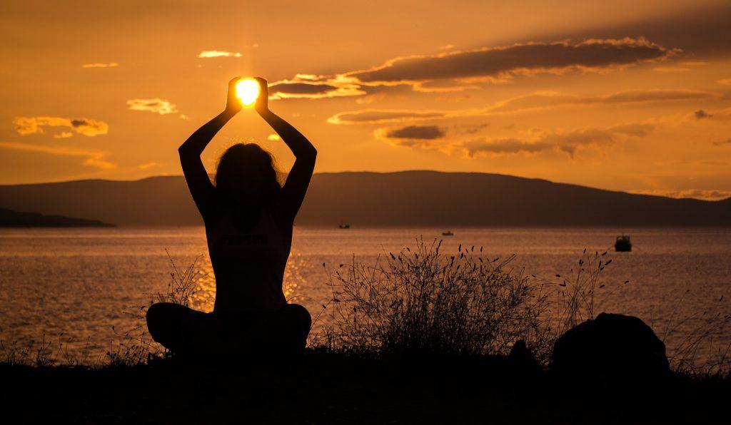 persona in posizione di yoga al tramonto